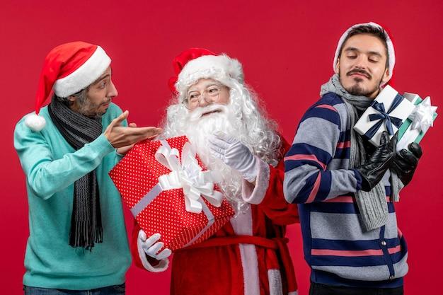 Vista frontale babbo natale con due maschi che tengono regali sull'emozione rossa regalo di capodanno rosso natale