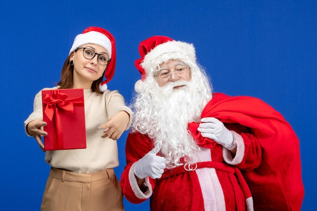 青い休日の感情の色でプレゼントバッグを運ぶ若い女性と正面のサンタクロース