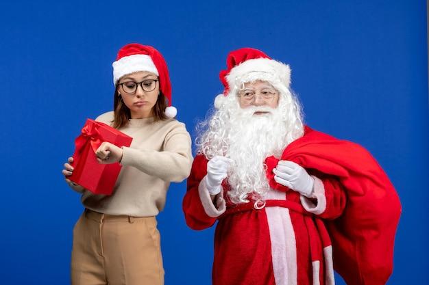 青い休日の精神の感情にプレゼントバッグを運ぶ若い女性と正面のサンタクロース