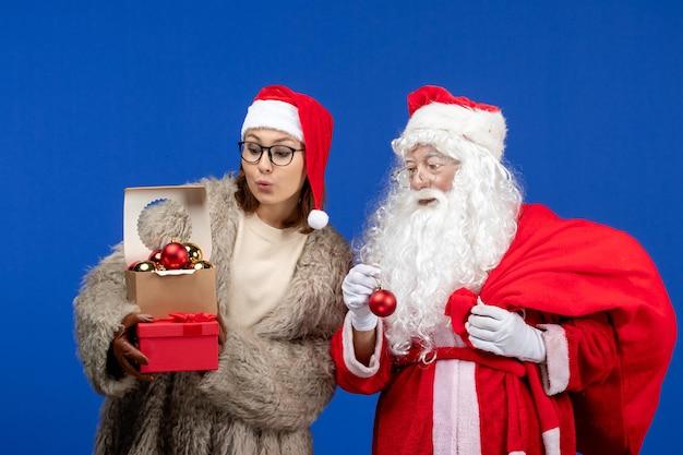 Vista frontale babbo natale con giovane borsa da donna con regali e giocattoli sul colore blu di natale
