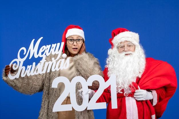 메리 크리스마스와 푸른 휴일에 글을 들고 젊은 여성과 전면보기 산타 클로스