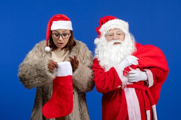 파란색 책상 휴일 크리스마스에 선물 가방과 빨간 양말을 들고 있는 젊은 여성이 있는 전면 전망 산타클로스