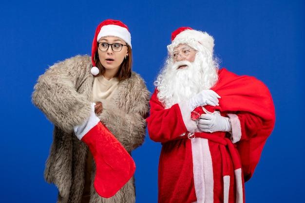 青い休日のクリスマスにプレゼントバッグと赤い靴下を保持している若い女性と正面のサンタクロース