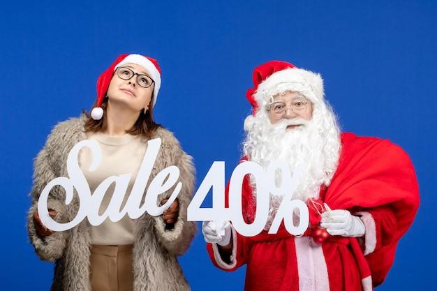 青い休日のクリスマスの色の新年にセールの執筆を保持している若い女性と正面のサンタクロース