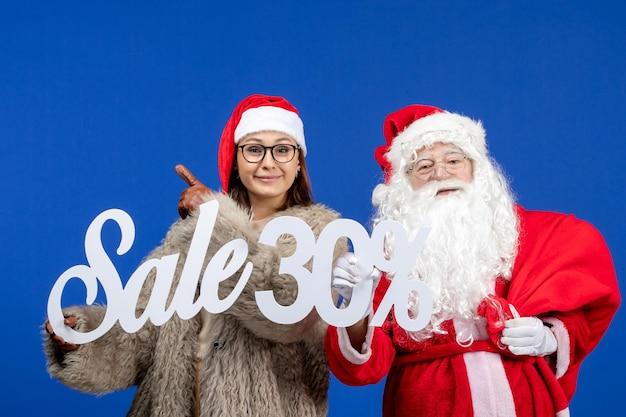青い休日のクリスマスの新年の色でセールの執筆を保持している若い女性と正面のサンタクロース