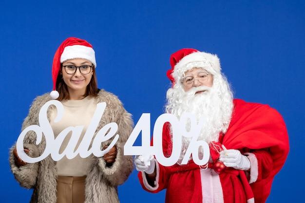 青い休日のクリスマスの色で販売の執筆を保持している若い女性と正面のサンタクロース