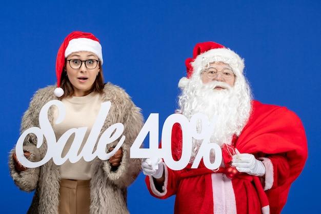 青い休日のクリスマスにセールの執筆を保持している若い女性と正面のサンタクロース