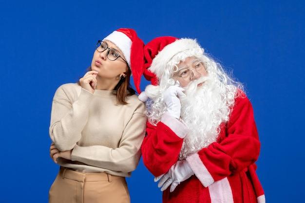 青い色の雪のクリスマス新年の感情を考えている若い女性と正面のサンタクロース