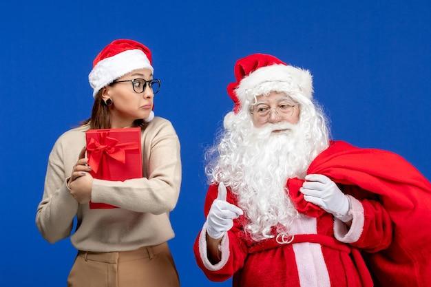 青い休日の感情の色でプレゼントを保持している若い女性と正面のサンタクロース