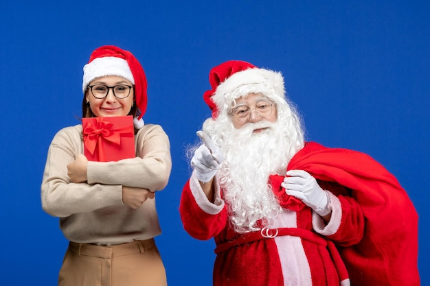 Front view santa claus with young female whos holding present on a blue holiday emotion color