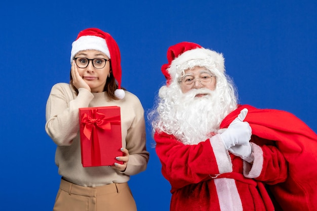 Front view santa claus with young female whos holding present on blue holiday emotions color