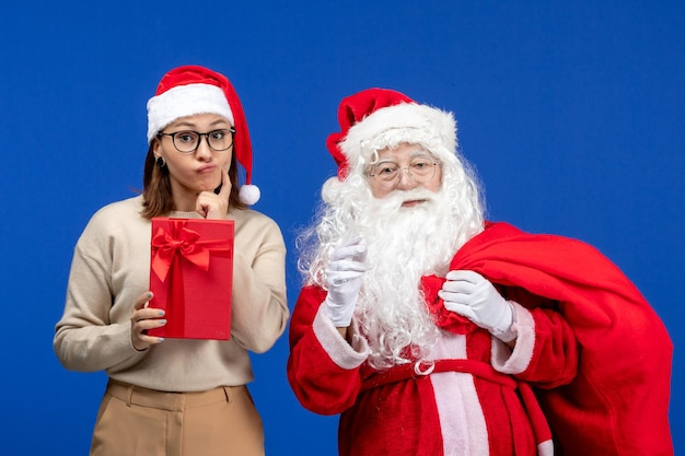 Front view santa claus with young female whos holding present on a blue holiday snow emotion color