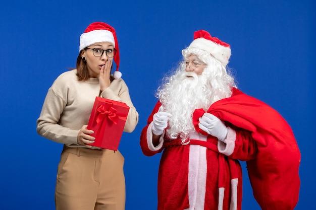 青い休日の精神の感情にプレゼントを保持している若い女性と正面図のサンタクロース