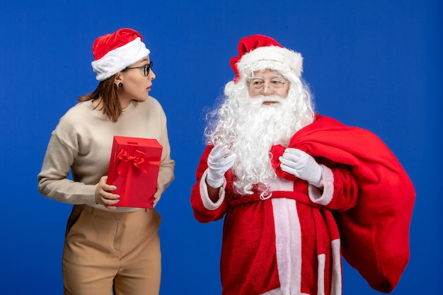 青い色の休日の精神の感情にプレゼントを保持している若い女性と正面図のサンタクロース