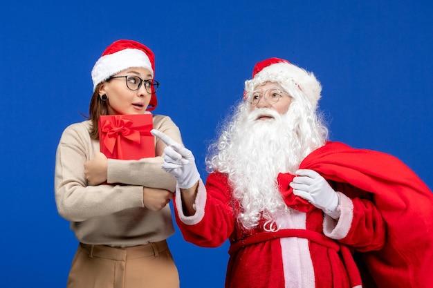 青い机の上にプレゼントを持っている若い女性の正面図サンタクロース休日感情色クリスマス雪の精神