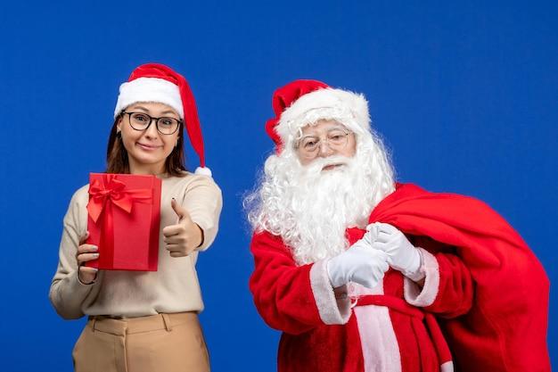 青い机の休日の雪の感情にプレゼントを保持している若い女性と正面のサンタクロース