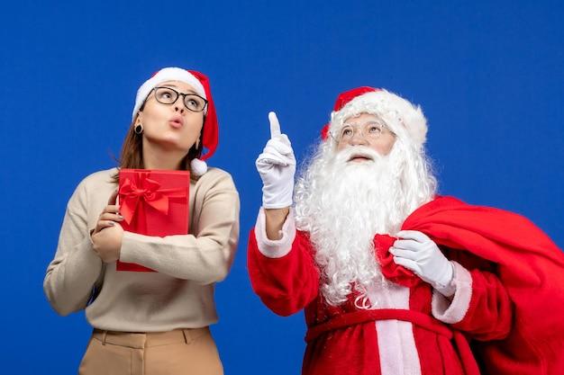 青い床の休日の感情の色でプレゼントを保持している若い女性と正面図のサンタクロース