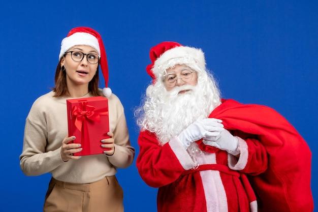青い床の休日の雪の感情にプレゼントを保持している若い女性と正面のサンタクロース