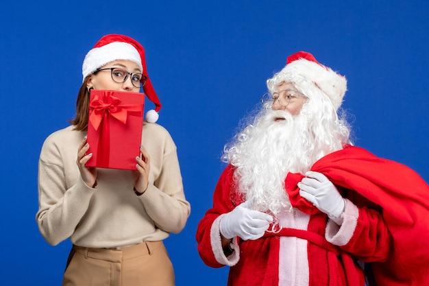 青い休日の感情の色のクリスマスの雪の精神にプレゼントを保持している若い女性と正面図のサンタクロース