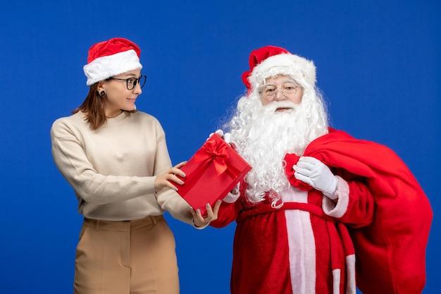 青い休日の雪の色のクリスマスの精神にプレゼントを保持している若い女性と正面図のサンタクロース