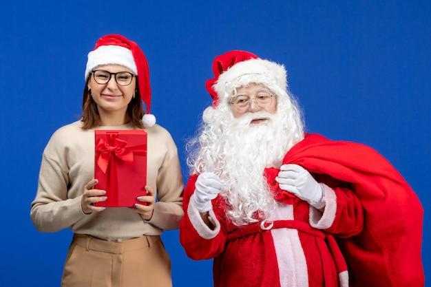 青い休日の雪の感情の色でプレゼントを保持している若い女性と正面図のサンタクロース