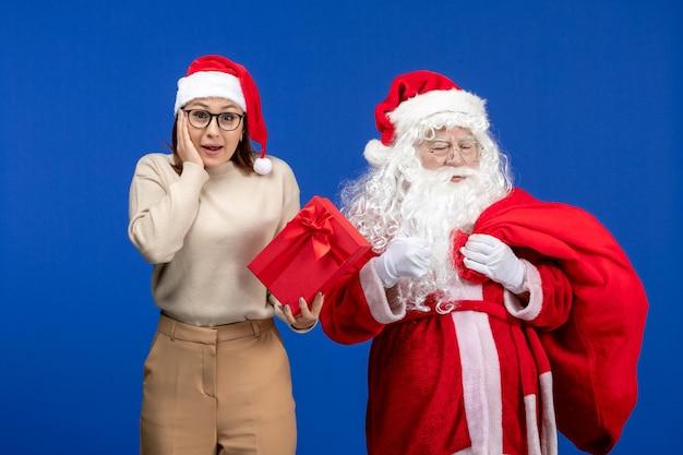 青い休日の精神の雪の色でプレゼントを保持している若い女性と正面図のサンタクロース