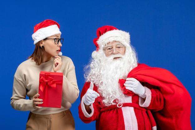 青い休日の雪の感情にプレゼントを保持している若い女性と正面のサンタクロース