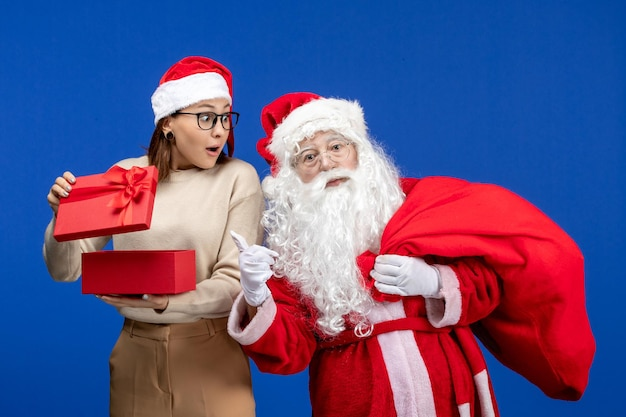 Front view santa claus with young female whos opening present on blue floor holiday snow emotion