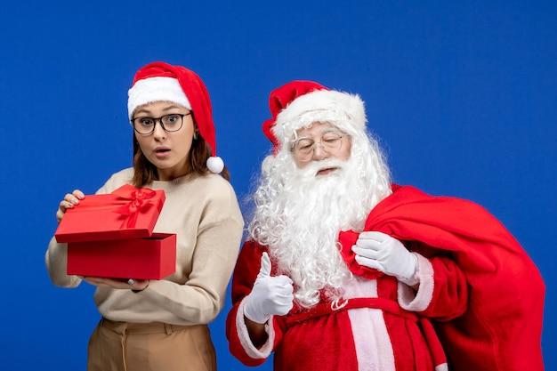 青い休日の雪の感情の色でプレゼントを開く若い女性と正面図のサンタクロース