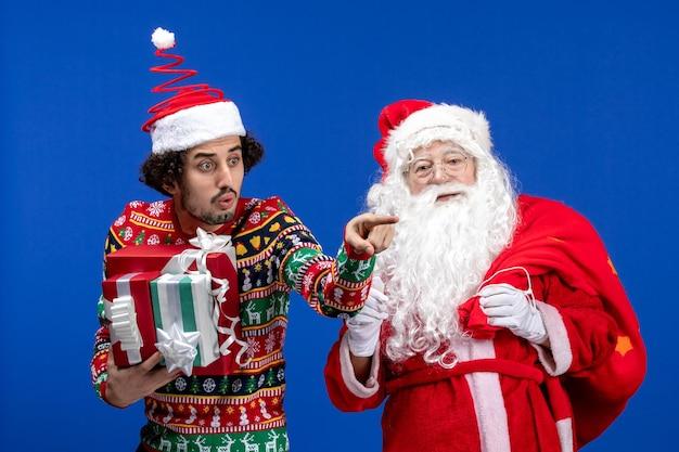 若い男性と青い色のクリスマスの休日の感情にさまざまなプレゼントと正面のサンタクロース