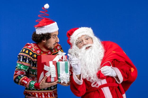 若い男性と青い感情のクリスマスの休日の色のさまざまなプレゼントと正面のサンタクロース