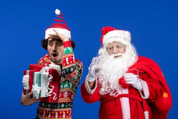 若い男性と青い床の休日の感情のクリスマスの色にさまざまなプレゼントと正面のサンタクロース
