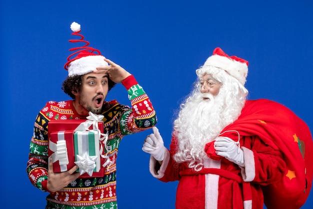 若い男性と青い休日の感情のクリスマスの色のさまざまなプレゼントと正面のサンタクロース