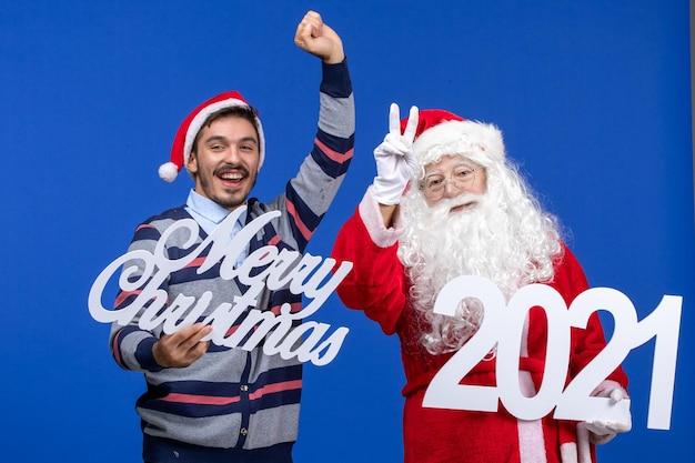 블루 크리스마스에 젊은 남성 들고와 메리 크리스마스 글과 전면보기 산타 클로스