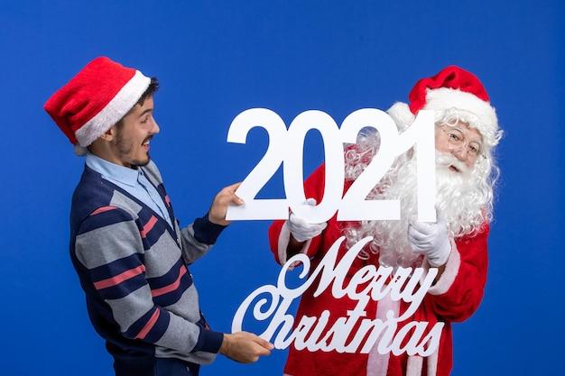 若い男性が保持している正面図のサンタクロースと青い新年のメリークリスマスの執筆
