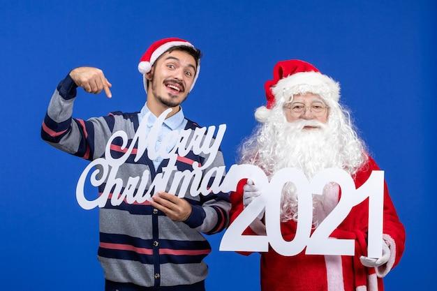 若い男性が青いクリスマスの休日にメリークリスマスの執筆を保持している正面図のサンタクロース