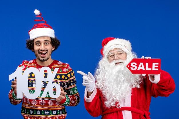 青い雪の色の新年のクリスマス休暇に若い男性の保持と販売の執筆と正面図のサンタクロース