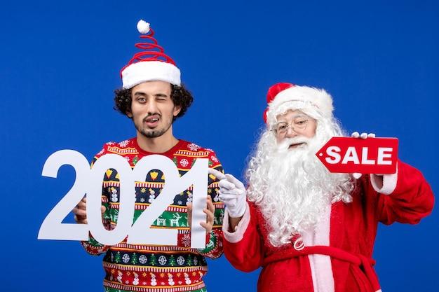 青い雪の色の新年のクリスマスに若い男性の保持と販売の執筆と正面図のサンタクロース