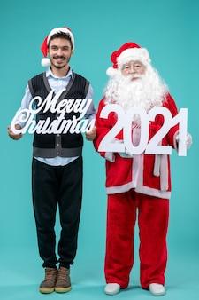 파란색 배경에 메리 크리스마스와 글을 들고 젊은 남성과 전면보기 산타 클로스