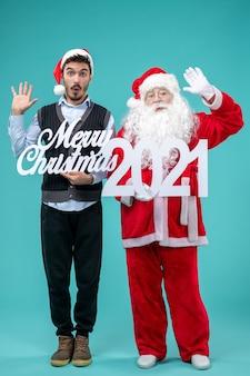 메리 크리스마스와 파란색 바닥 색 눈 새 해 휴일 크리스마스에 글을 들고 젊은 남성과 전면보기 산타 클로스