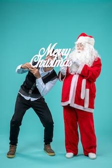 青い背景にメリークリスマスの書き込みを保持している若い男性と正面のサンタクロース