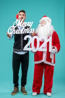 Front view santa claus with young male holding merry christmas and writings on blue background
