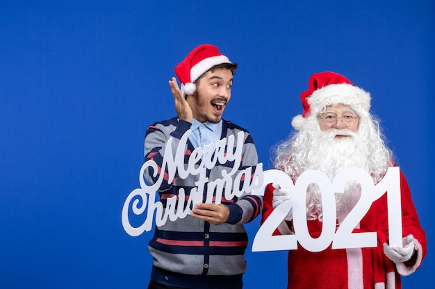 Front view santa claus with young male holding and merry christmas writings on blue xmas holidays
