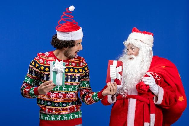 Vista frontale babbo natale con i giovani maschi che tengono i regali