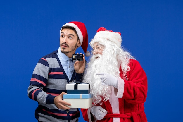 Front view santa claus with young male holding presents
