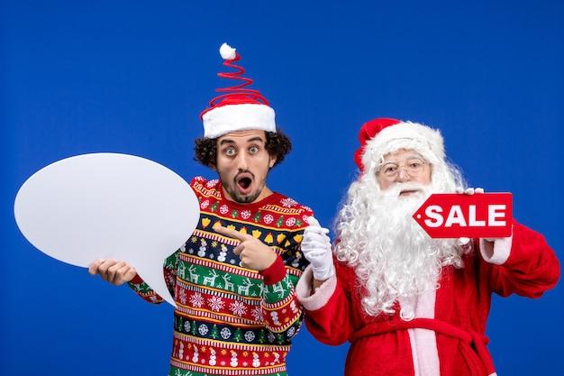 젊은 남성 흰색 기호 및 판매 쓰기를 들고와 전면보기 산타 클로스