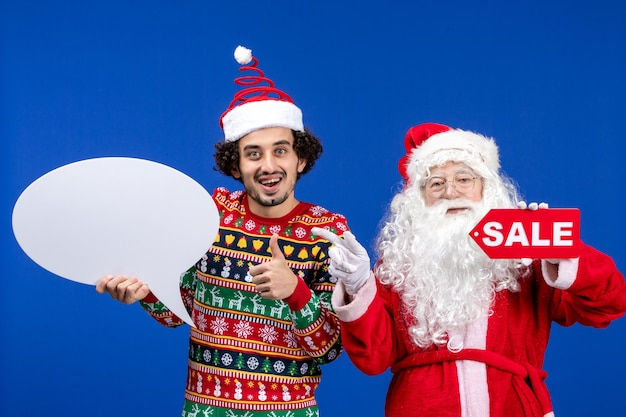 Front view santa claus with young male holding white sign and sale writing
