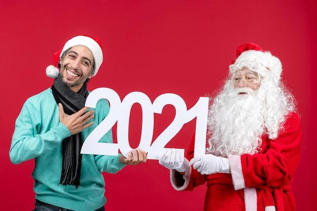 赤い新年のクリスマス休暇の感情のプレゼントに書き込みを保持している若い男性と正面のサンタクロース