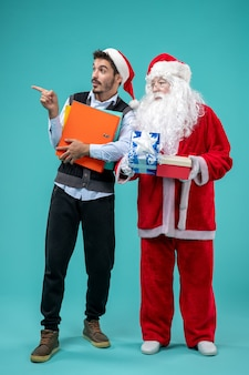 Front view of santa claus with young male and presents on blue wall