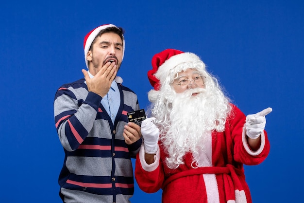 Front view of santa claus with young man holding bank card on blue wall